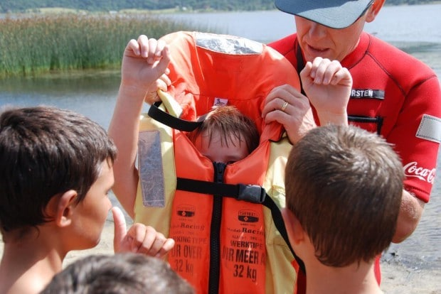 Image of a man teach children how to properly fit a life jacket.