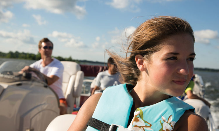 girl sitting in boat with lifejacket on and father in background