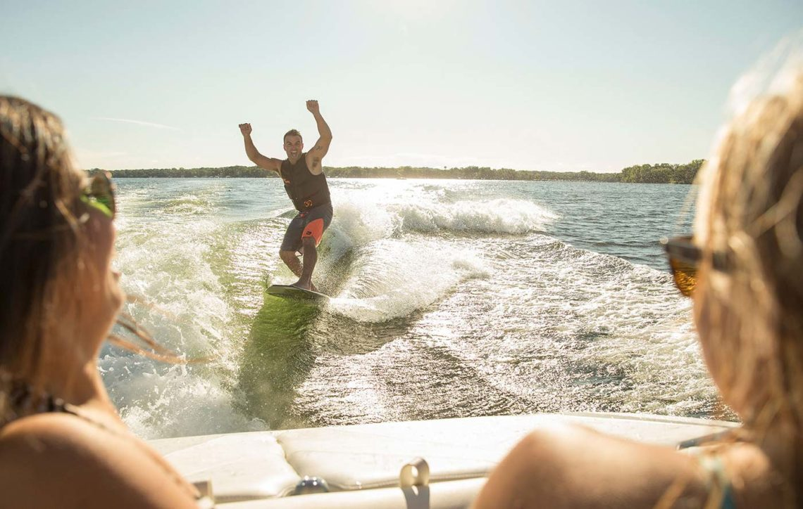 Dude wake surfing with hands in the air