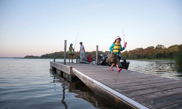 Girl carrying tackle box on dock with parents in background