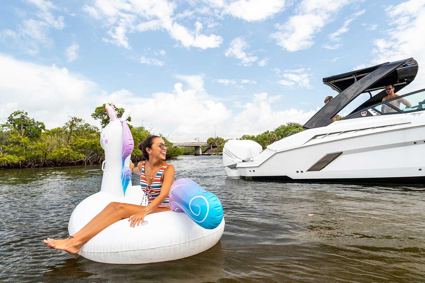 girl sitting on inflatable unicorn floating next to boat