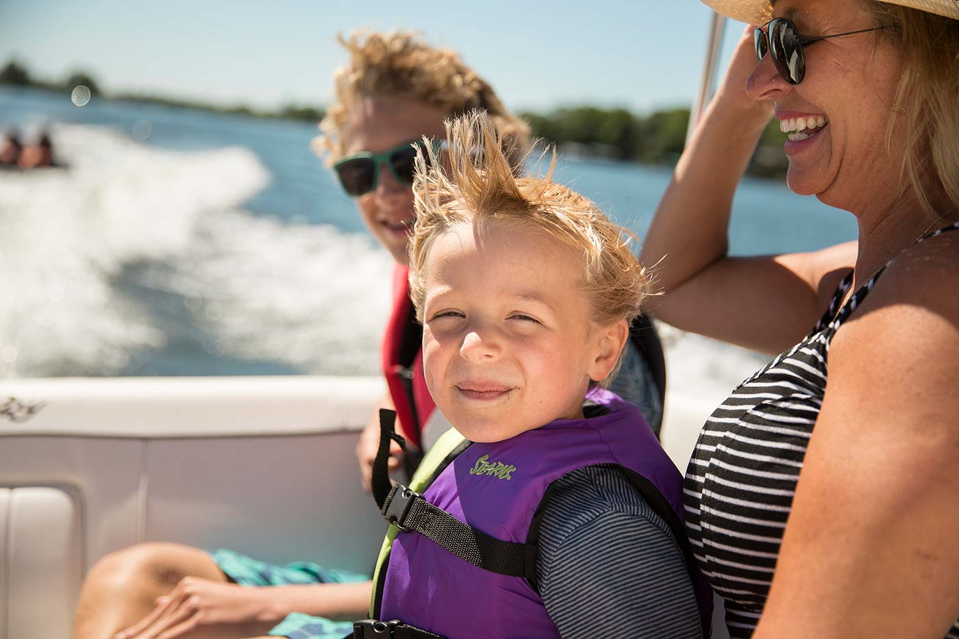 two kids in lifejackets sitting with grandparent on boat