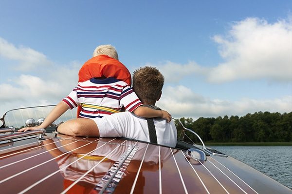Father and son enjoying a boat ride after buying a boat for the first time.