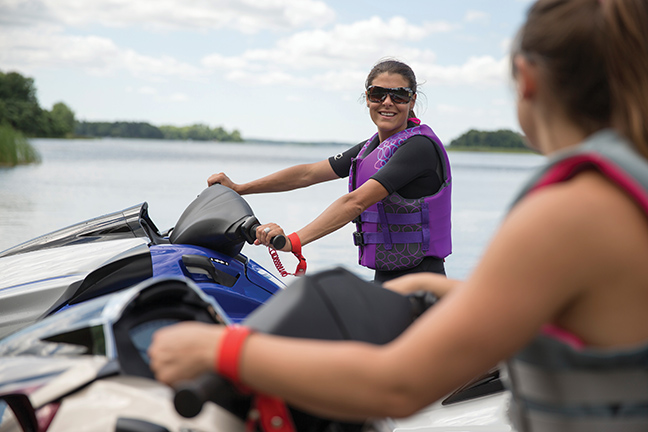 Two women on jetskis chatting from a distance