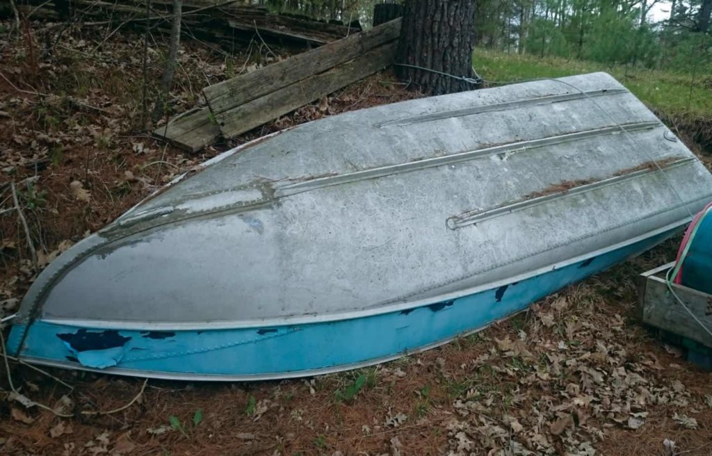 Image of an old tin boat laying up side down in a wooded area, ready to be refurbished for a DIY project. .
