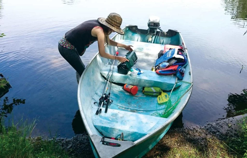Image of a woman loading a tin fishing boat with gear, after the completion of the DIY project.