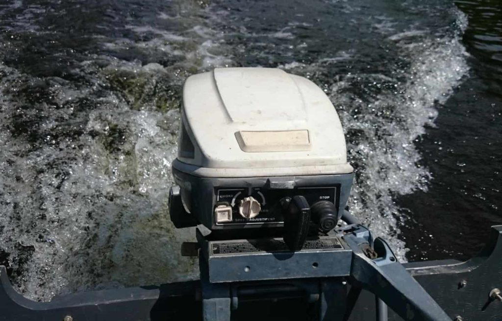 Image of an outboard boat engine, attached to a boat, while operating.