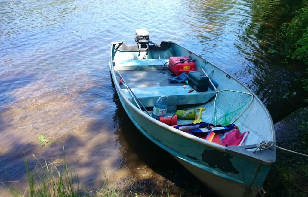 Image of the refurbished tin boat in the water loaded with gear and equipment.