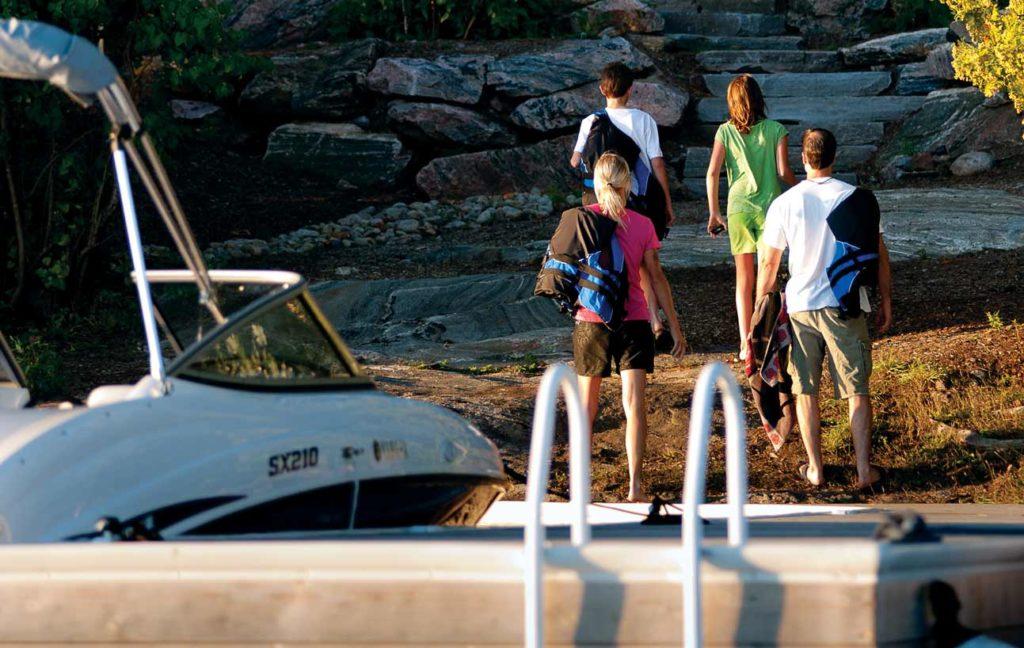 family arriving at cottage via boat